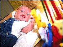 Baby on changing mat in nursery