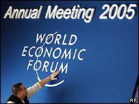 Un hombre termina de arreglar el logo del Foro Económico Mundial.