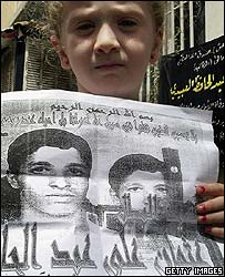A relative of Othman Abdul Hafez holds up a photocopied article about his exploits