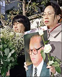 Protestors, holding a portrait of former Chinese Communist Party chief Zhao Ziyang and flower bouquets, stand before the Chinese embassy in Tokyo 21 January 2005.