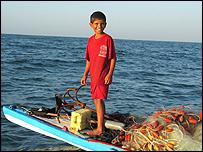 Boy on a skiff off the coast of Gaza. Photograph by George Azar