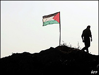 Palestinian security official plants flag near the former Netzarim Jewish settlement