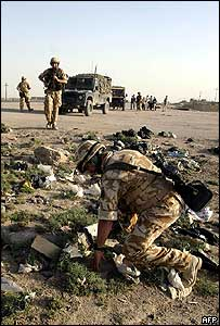 A British soldier inspects the site of the blast that earlier killed two colleagues