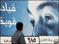An Iraqi boy walks past an election poster supporting Iraqi Interim Prime Minister Iyad Allawi in Basra