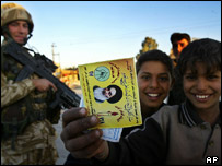 Iraqi youngsters displays an election pamphlet watched by a British soldier on patrol in the southern Iraqi city of Basra