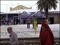 People walk past melting snow