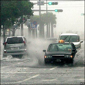 Vehicles drive through a flooded road in Kagoshima, 06 September 2005