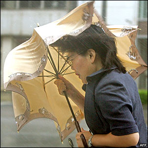 A woman walks in strong winds and heavy rain in Kagoshima, 06 September 2005.