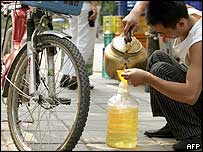 A man filters petrol to fill his moped outside a filling station in Beijing 30 August 2005