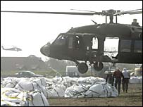 A US military helicopter takes sandbags to damaged flood defences