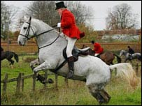 A mounted huntsman jumps a fence