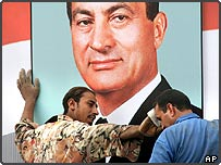 Egyptian man wipes his colleagues brow as they put up poster of Hosni Mubarak in Cairo, Egypt