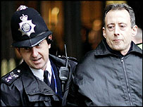 Police officer leading Peter Tatchell away from Westminster Hall