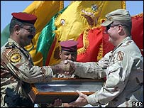 The US commander hands over the keys to the base to his Iraqi counterpart