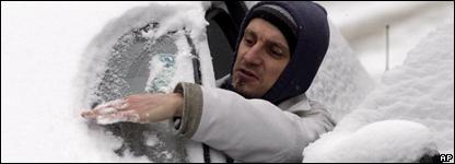 Un hombre limpia la nieve de los cristales de su vehículo