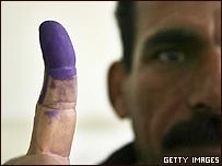 Un votante iraquí muestra su dedo untado de tinta