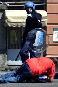 An Italian riot policeman stands over a protester