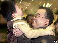 Taiwanese businessman Tony Chou hugs his son Chou Chi-huei, 7, at Taiwan's airport after the first direct flight - from Guangzhou on the mainland - touched down on Saturday
