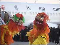Lion dancers perform as passengers board the first passenger flight from Beijing to Taiwan on Saturday