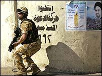 Soldado británico en Basora junto a afiches electorales