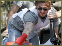 Actor Sean Penn bails water out of a boat as he attempts to rescue people stranded by Hurricane Katrina in New Orleans