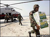 A Mississippi National Guardsman carries aid supplies