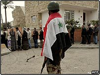 Iraqi soldier in national flag guards line of voters at Baghdad polling station