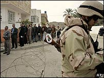An Iraqi army soldier guards a queue of voters in Baghdad