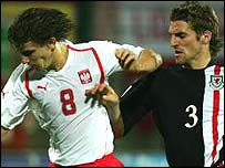 Wales left wing-back Sam Ricketts puts pressure on Poland's Radoslaw Sobolewski