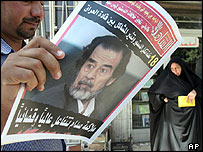 Baghdad man reads newspaper featuring an article about Saddam Hussein's impending trial