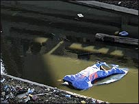 A dead body is covered with a tarp and marked with an X beneath an overpass