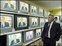 Ukrainians watch TV in a shop as Mr Yushchenko announces the sacking of the cabinet
