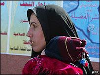Mujer iraquí pasa con un niño frente a un cartel electoral.