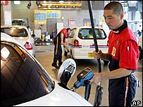 Attendant at a Japanese petrol station filling up a car