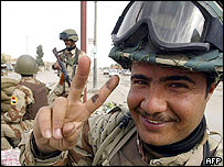 An Iraqi soldier flashes the victory sign as he secures a street in the city of Najaf