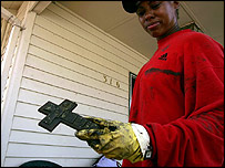 Roslyn Green holds up a cross found in her family's flood-damaged home in Biloxi, Mississippi