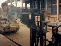L/Cpl Cooley driving a forklift with an Iraqi tied to the fork
