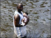 A man carries a baby through the flooded streets of New Orleans