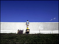 Woman peeks over a dry section of New Orleans' fateful 17th Street Canal floodwall