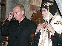 Vladimir Putin makes the sign of the cross beside Meliton of Philadelphia at the Mount Athos monastic community