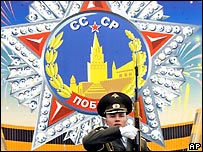 Солдат марширует на фоне изображения Ордена победы