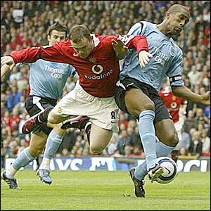 Wayne Rooney is tackled by Sylvain Distin