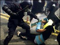 A policeman beats a protester