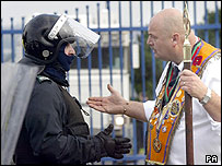Orangeman arguing with police officer
