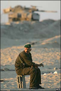 A Palestinian policeman on guard by an Israeli tank, near Khan Younis in Gaza