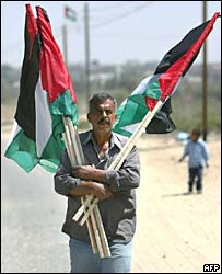 A Palestinian man carries national flags through the streets of Rafah