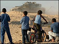 Ni�os palestinos observan un tanque israel� junto al asentamiento de Neve Dekalim, en Gaza