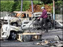 A cyclist makes his way through burnt out vehicles