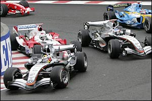 Jarno Trulli forces Kimi Raikkonen wide at the first corner