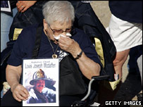 A mourner holds up a picture of New York City Fire Department Battalion Chief, Louis Joseph Modafferi